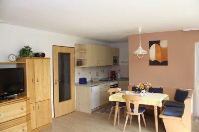 Küche mit Eßecke mit Blick auf Wohnzimmerteil und Türe zum Balkon.