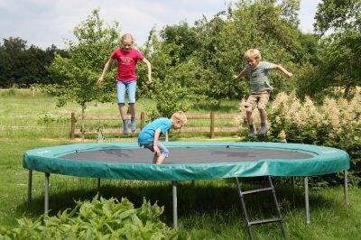 Das Trampolin steht im großen Garten und läd zum Toben ein.